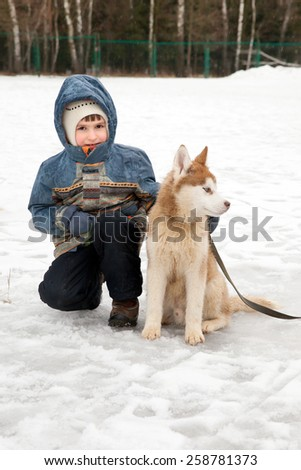 a child with a dog on a walk - stock photo