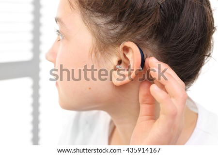 A child with a hearing aid. The girl assumes hearing aid. - stock photo