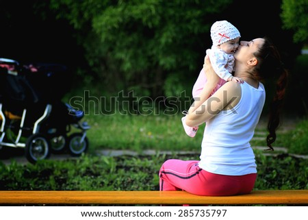 a child with her mother sitting on a bench - stock photo