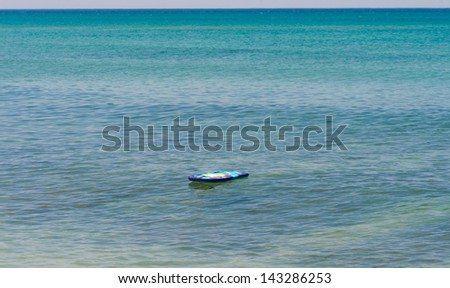 A children's surfboard floating in the middle of the sea. The surfer is absent. - stock photo