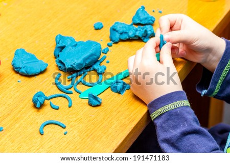 A Childs hands holding Play Doh - stock photo