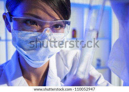 A Chinese Asian female medical or scientific researcher or doctor looking at a test tube of clear liquid in a laboratory. - stock photo