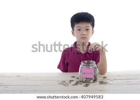 A chinese boy putting coin into a glass jug as saving - stock photo