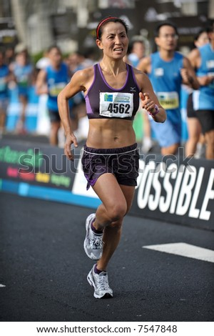 A Chinese female athlete completing the Singapore Marathon 2007 - stock photo