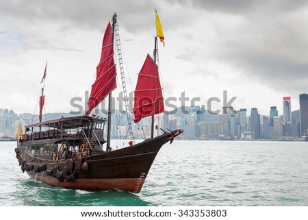 A Chinese junk ship with red sails on Victoria Harbor in Tsim Sha Tsui, Kowloon, with Hong Kong's downtown financial district in the background.  - stock photo