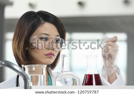 A Chinese scientific researcher holding at a liquid solution in a lab. - stock photo