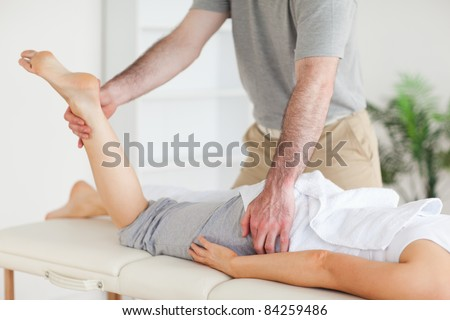 A chiropractor stretches a female customer's leg in his surgery - stock photo