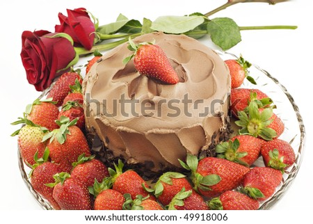 A chocolate cake surrounded by fresh strawberries and red roses on horizontal white background, copy space - stock photo