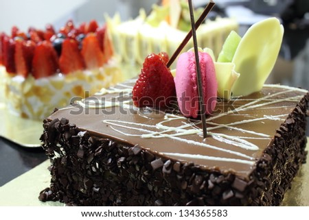 A Chocolate cake topped with a strawberry and  macaron - stock photo