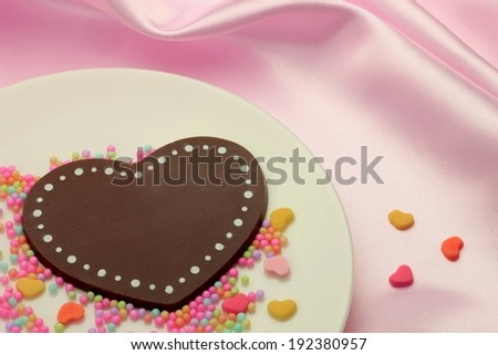 A chocolate heart surrounded by candies on a plate. - stock photo