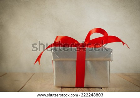 A Christmas gift box with closed lid, wrapped in silver paper and tied to a bow with a red satin ribbon.  Placed on a weathered old wooden table with copy space to left and above. Vintage style. - stock photo