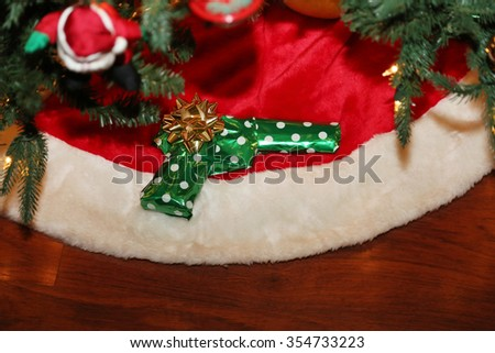 A Christmas Present of a Hand Gun or Pistol Wrapped in green wrapping paper with a gold bow under a Christmas tree. 2015 saw a 25% increase in gun sales for the Christmas Holiday Season.  - stock photo