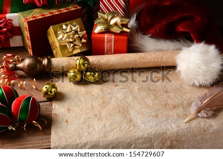 A Christmas Still Life with an old parchment scroll, presents, ornaments and a Santa Hat. Closeup in horizontal format with strong side light.  - stock photo