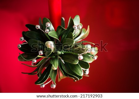A Christmas tradition. A ball of artificial mistletoe against a red background.  - stock photo