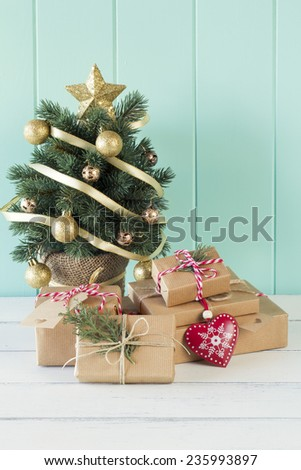 A christmas tree and some paper parcels wrapped tied with tags. A red heart and some christmas gift boxes wrapped with paper kraft and tied with red & white baker's twine. Vintage Style. - stock photo