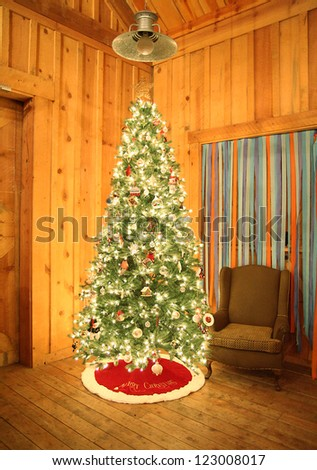 a christmas tree in a barn, set up for a celebration party - stock photo