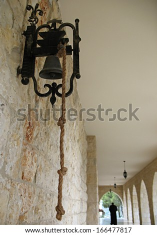A church bell with a monk walking away in the background. Taken in Lebanon. - stock photo