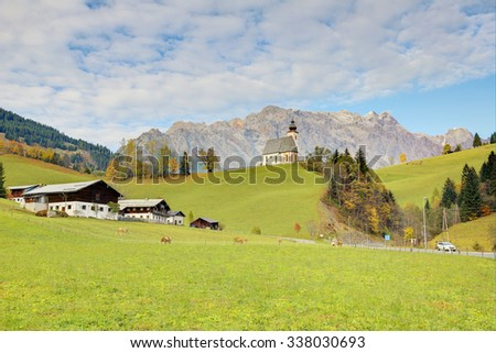 A church high on the hilltop with a mountain range in the background and a grassy ranch in the foreground ~ Autumn scenery of St. Nikolaus Church of Dienten Village and Hochkoenig Mountains in Austria - stock photo