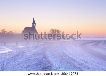 A church in a frozen winter landscape in The Netherlands. Photographed at sunrise on a beautiful foggy morning. - stock photo