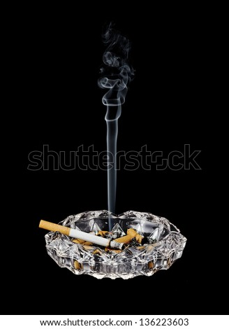 A cigarette burns shorter in a glass ashtray - stock photo