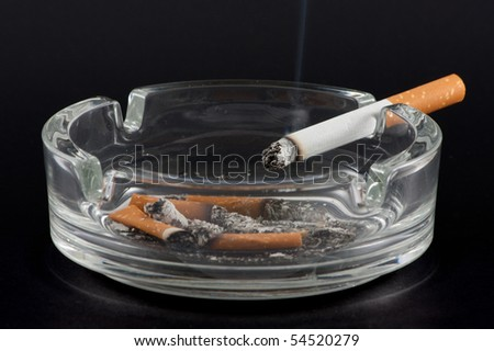 A cigarette on the edge of a typical ashtray (some cigarette butts and ashes inside). - stock photo