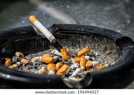 A cigarette with ash end rests on the side of a nearly full and dirty ashtray containing much ash and many crushed cigarette butts. - stock photo