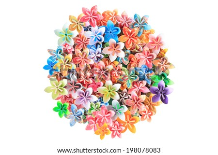 A circle pile of colorful paper flowers on a white background - stock photo