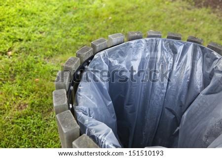 A circular trash bin and grass background. - stock photo
