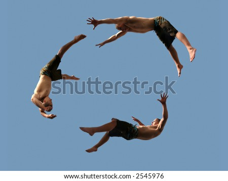 A cirlcle of three flying young athletic men - stock photo