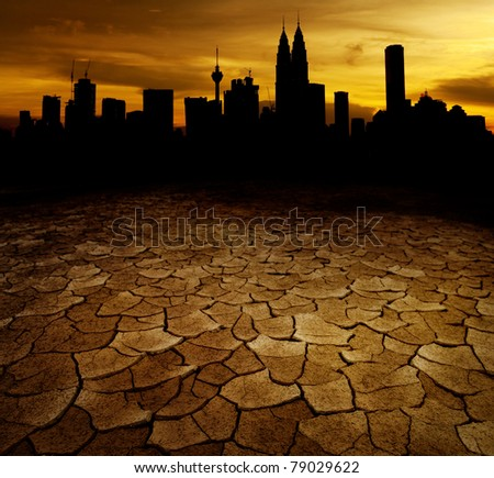 A city looks over a desolate cracked earth landscape in sunset - stock photo