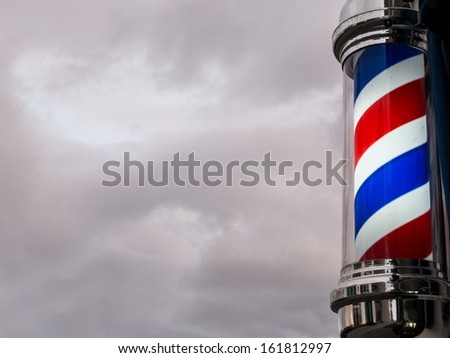 A classic barber pole set against a clouded sky background that is perfect as copy-space. - stock photo