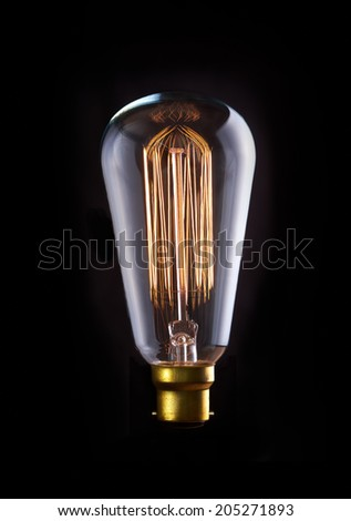 A classic Edison light bulb with a squirrel cage filament. Switched On. - stock photo