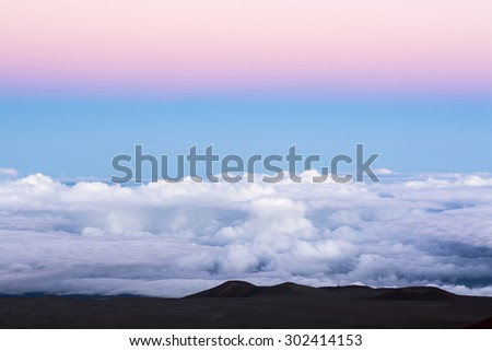 A classic pink inversion layer above a blue sky at 14,000 feet overlooking the top of the clouds. - stock photo