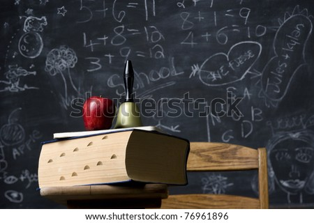 A classic still life of an antique school desk with huge dictionary and school bell against a blackboard. Horizontal shot. - stock photo