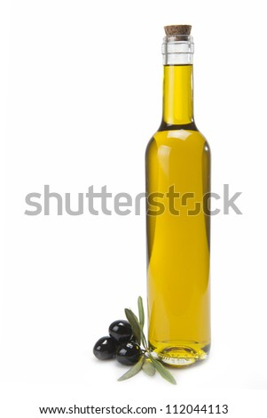 A classical glass bottle of olive oil and some black olives isolated over a white background - stock photo