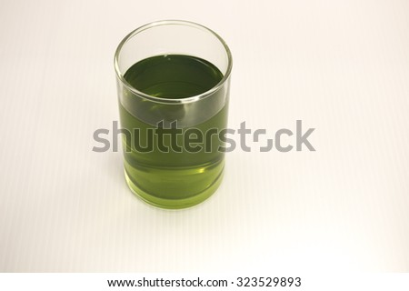 A clear glass of green color drink.  Green tea, pandan flavor drink, process sweeten wheat grass or others fleshly extracted juice.  Isolated on white background.  - stock photo