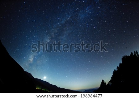 A clear night sky with a hill and trees in the foreground. - stock photo
