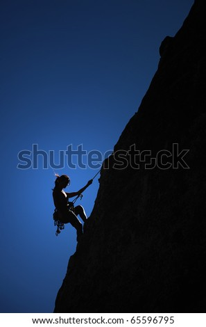 A climber hangs from a thread on the side of a cliff. - stock photo