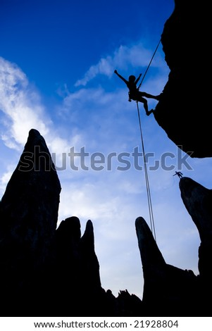 A climber rappelling from the summit of a rock spire is silhouetted against the evening sky in The Sierra Nevada Mountains. - stock photo