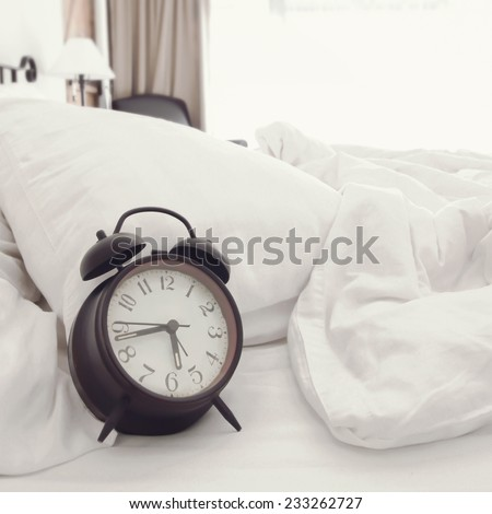 a clock on the bed (retro color) - stock photo