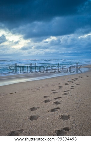 A close of footsteps in the sand during a cloudy sunset in Huntington Beach, California. - stock photo