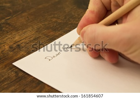 A close photo of a persons writing a letter with a pencil. - stock photo