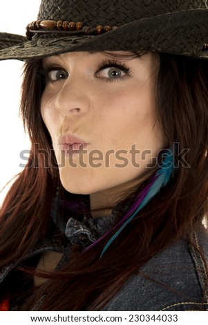 a close picture of a woman with her lips puckered in her cowgirl hat. - stock photo