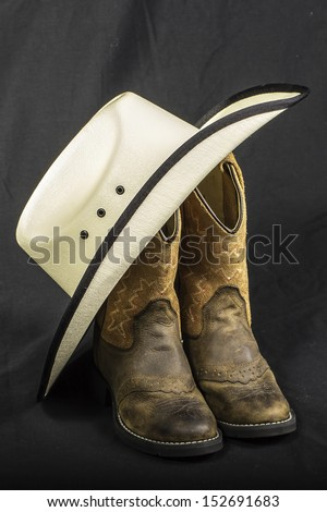 A close shot of a pair of boots and a cowboy hat. - stock photo