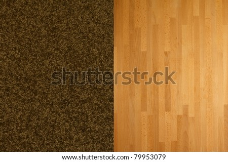 A close shot of plush pile carpet against a wooden floor - stock photo
