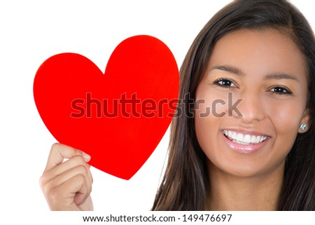 A close-up cropped image of a smiling young woman holding a heart, isolated on a white background  - stock photo