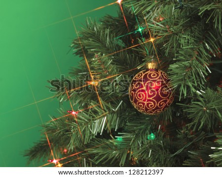 A close-up cropped image of Christmas tree with a red ball decoration - stock photo