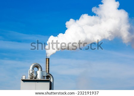 A close-up factory chimney smoking - stock photo