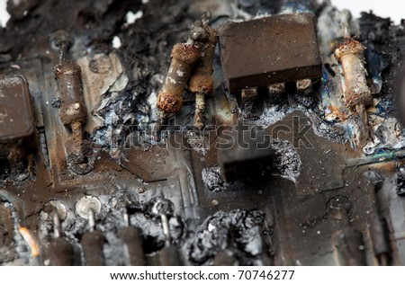 A close-up image of burnt components of a circuit board.  / BURNT CIRCUIT BOARD - stock photo