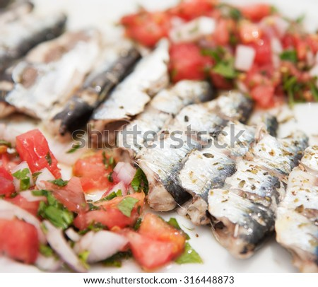 a close up in a dish with sardines baked fillet with vegetables in the blurry background (b) - stock photo